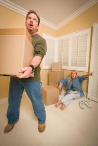 Stressed Man Moving Boxes for Demanding Wife Surrounded by Other Boxes.